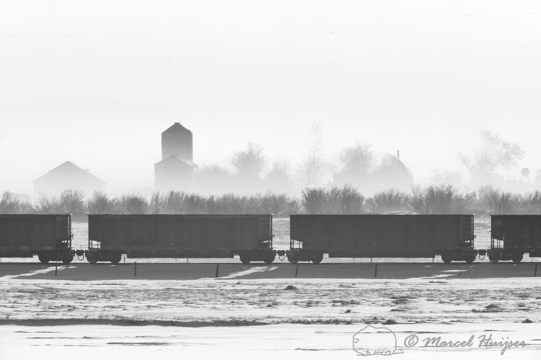 Cargo train and silo in fog, Montana, USA