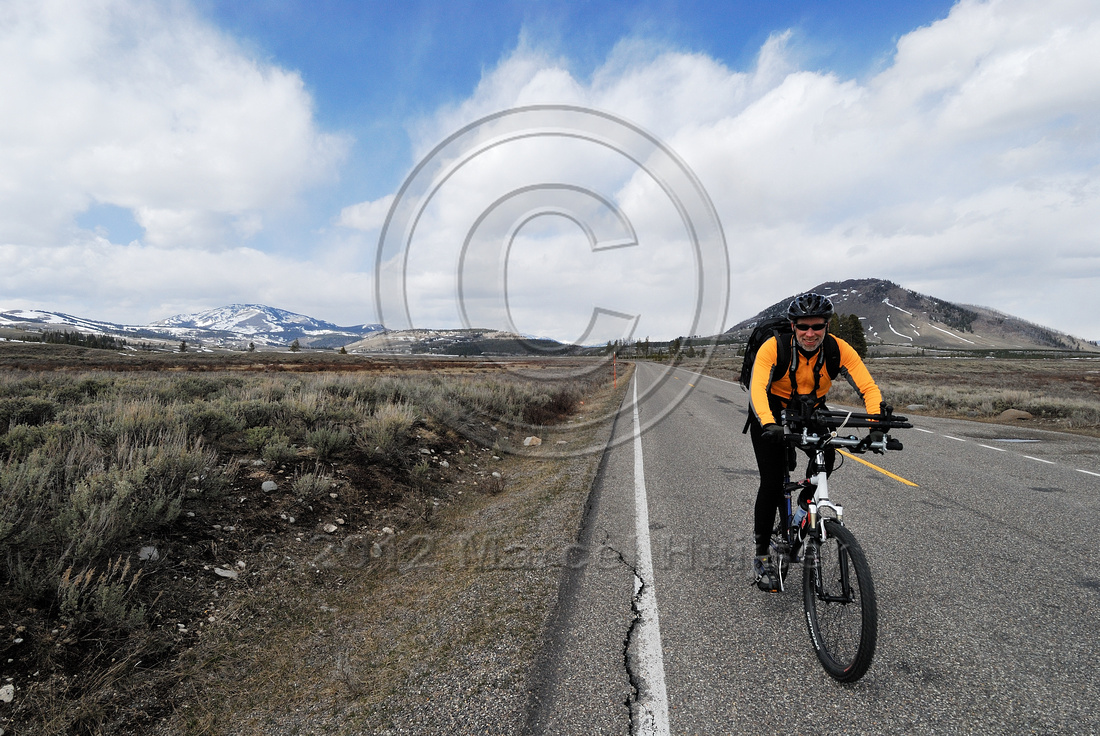 Bicyclist photographer with tripod attached to handlebars and camera backpack before roads open to motorized traffic in Yellowstone National Park, Wyoming, USA