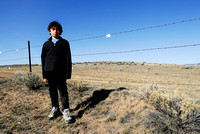 Emiliano Ferguson in front of livestock fence with markers for sage grouse