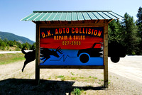 Auto repair advertisement sign with white-tailed deer and car on a collision course, near Trout Creek, Noxon Reservoir, Montana, USA