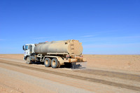 Water truck sprays water on road for dust control, Gobi, Mongolia