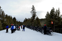 Line of snowmobiles parked along road to view wildlife, near West Yellowstone, Yellowstone National Park, Wyoming, USA