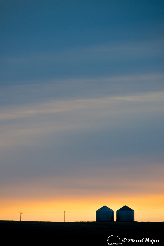 Silos silhoutted during sunrise, Montana, USA