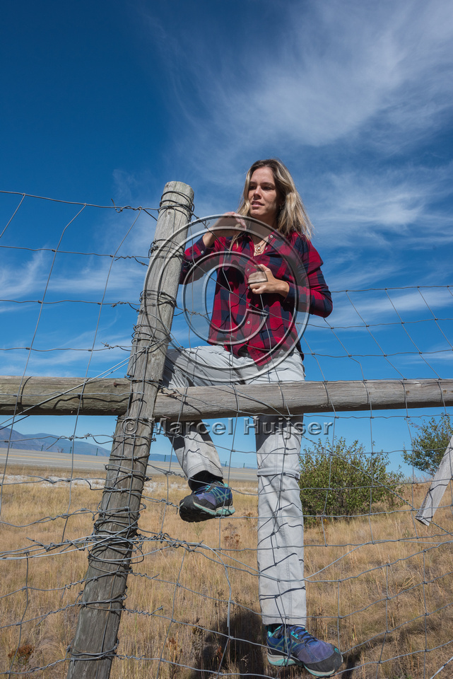 Fernanda Abra climbing a wildlife fence, north of Bonners Ferry,