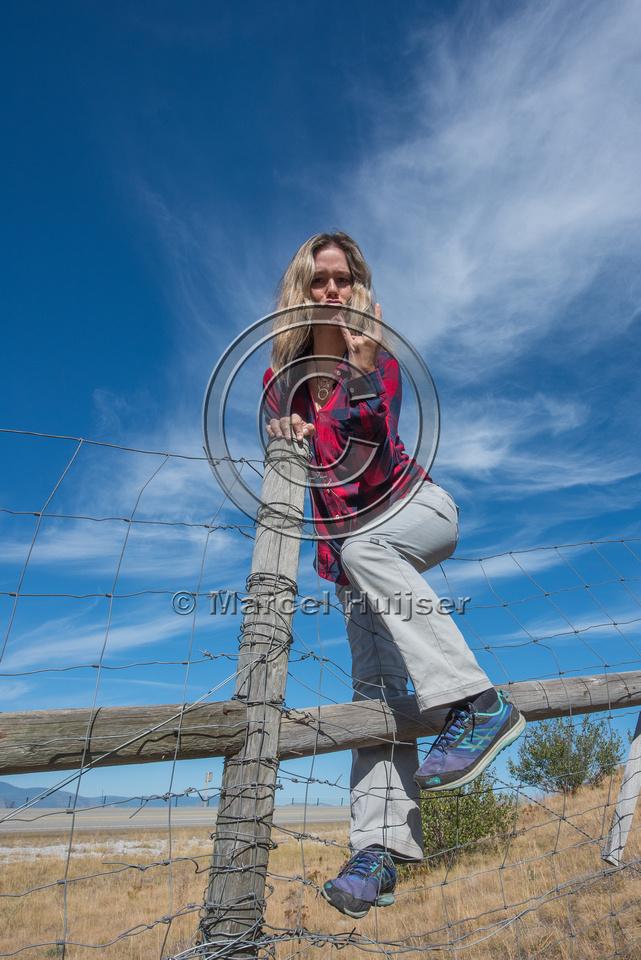 Fernanda Abra climbing a wildlife fence, north of Bonners Ferry,