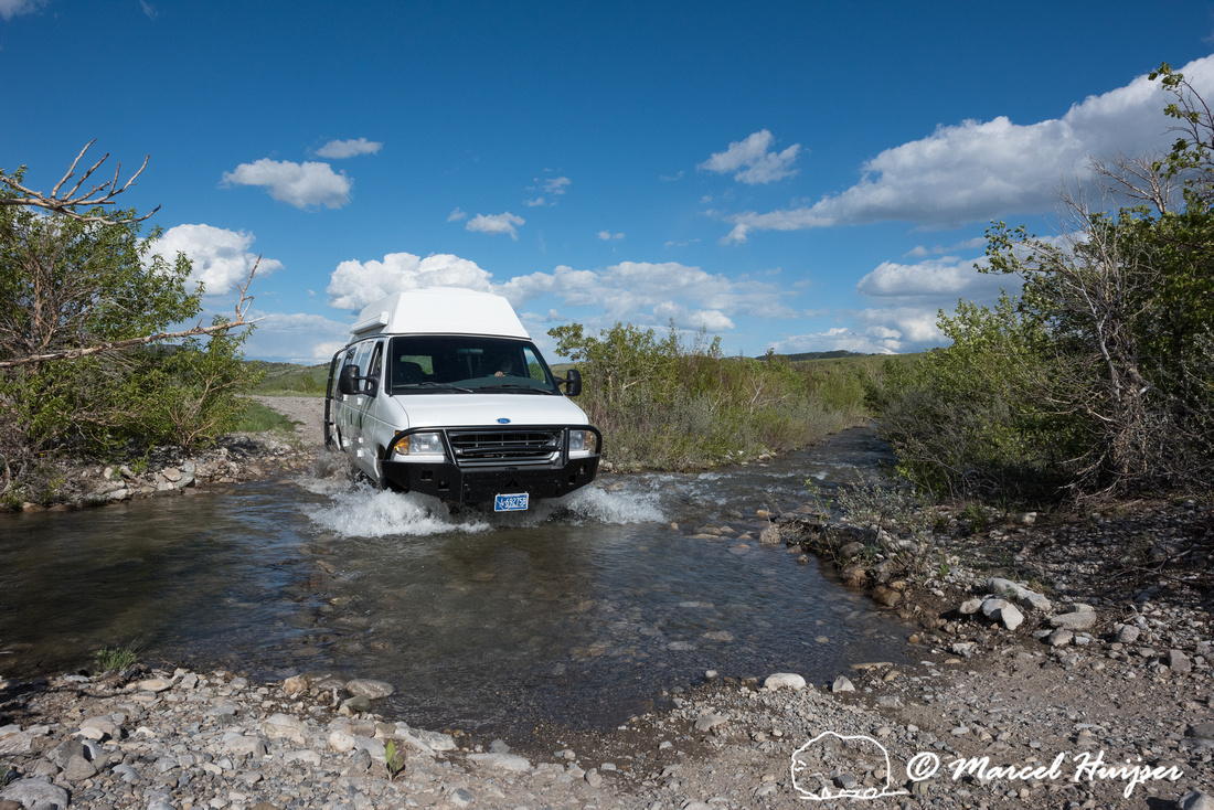 Our Ford E350 4x4 camper van on dirt road, crossing a creek, Mon