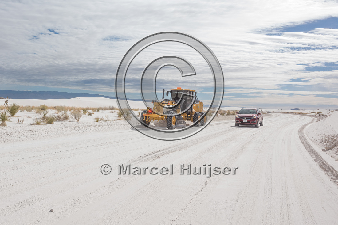 Grader clearing the road of sand (gypsum) in the morning, White
